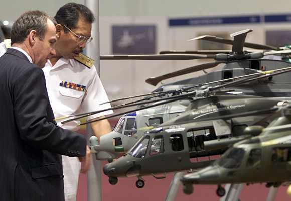 Visitors look at AgustaWestland model helicopters during Heli-Asia exhibition