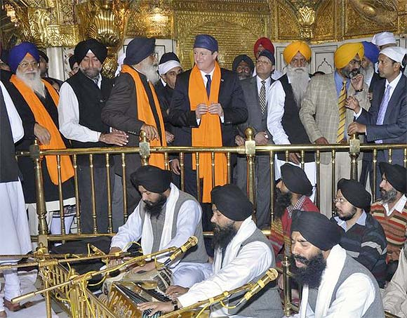 Britain's Prime Minister David Cameron speaks with Parkash Singh Badal, chief minister of Punjab, as he visits the holy Sikh shrine of Golden temple in Amritsar