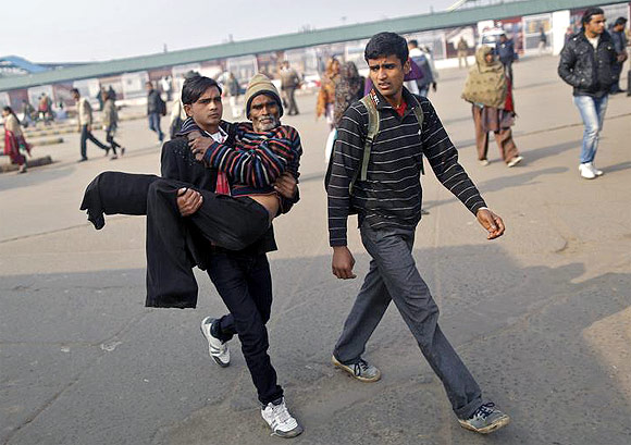 A man carries his sick father in his arms as no public transport was available outside Delhi railway station