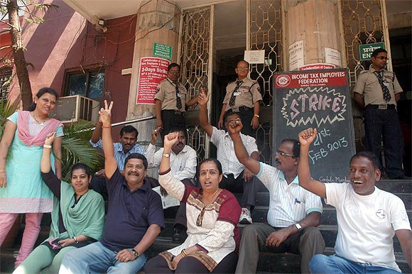 I-T department employees chant protest slogans outside a branch in Mumbai