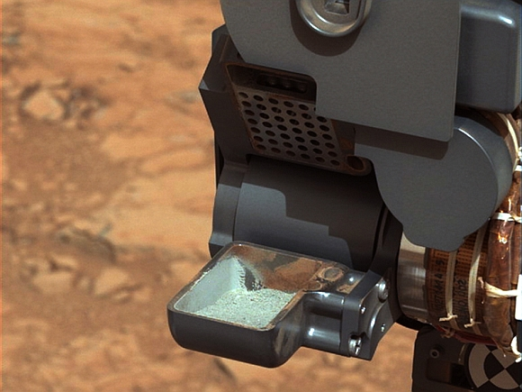 This image from NASA's Curiosity rover shows the first sample of powdered rock extracted by the rover's drill. The image was taken after the sample was transferred from the drill to the rover's scoop