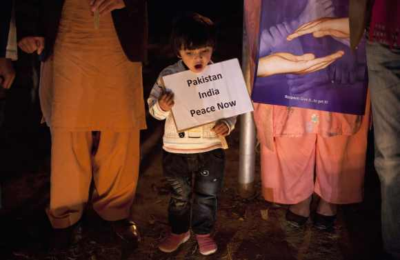 A girl holds a placard while observing a global vigil for peace between India and Pakistan
