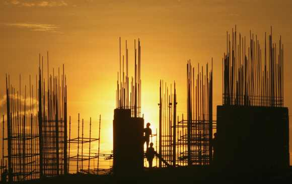 Labourers are silhouetted against the setting sun as they work at the construction site in Hyderabad