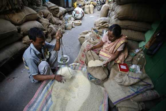 A shopkeeper weighs rice in a wholesale market in Kolkata