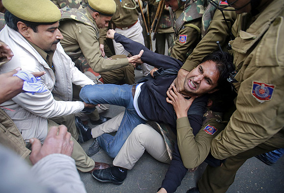 The police detain a demonstrator during a protest against the Delhi gang-rape
