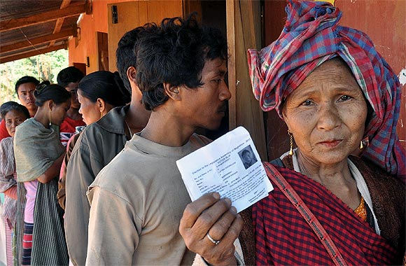 A woman shows her election card as she stands in a queue to vote
