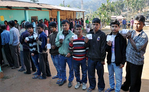 Youths display their identity card outside a poll booth