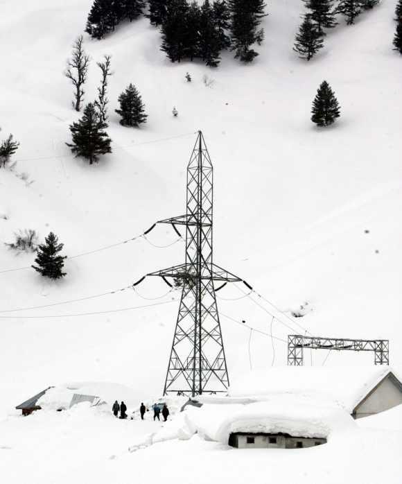Policemen stand amid deep snow near an electric transmission pylon in Kashmir