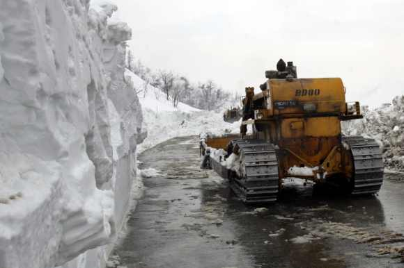 A bulldozer of Border Roads Organisation passes by a wall of snow on a key Kashmir highway
