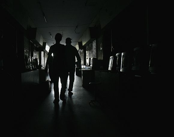 Men are silhouetted while they walking through a computer market during a power outage in Karachi