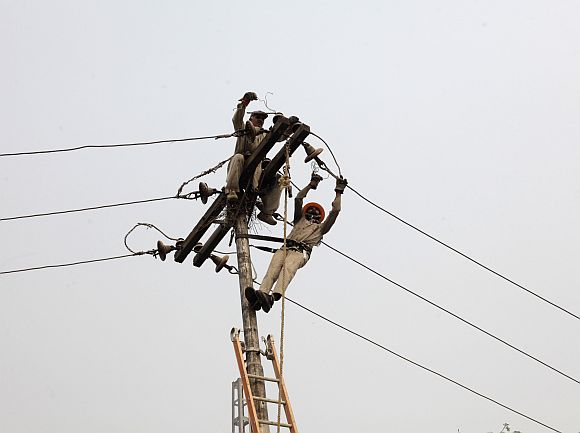 Technicians work on power lines supplying electricity in Lahore