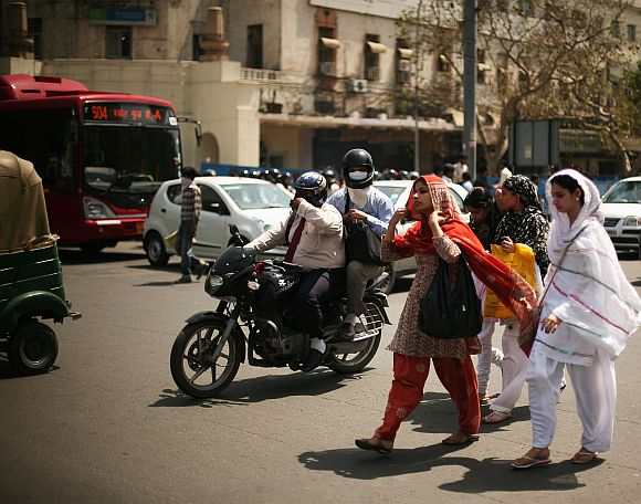 A motorcycle passes a group of ladies as they cross a street in New Delhi