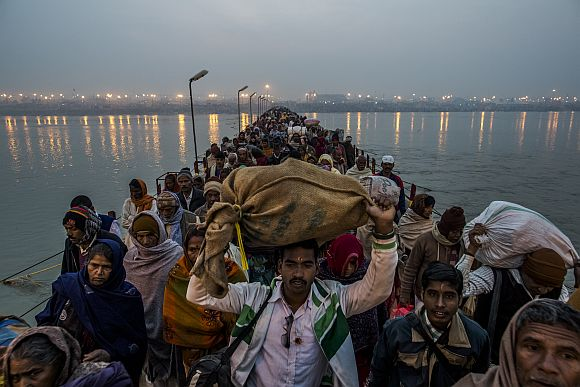 Pilgrims walk across a pontoon bridge as others bathe on the banks of Sangam