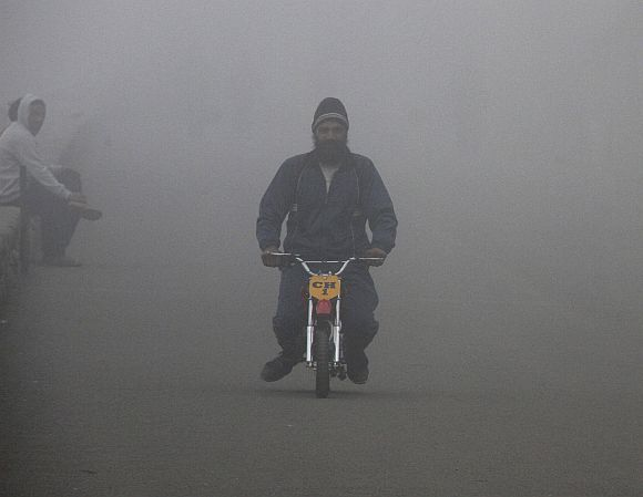 A man rides his mini bike amid dense fog on a cold winter morning in Chandigarh