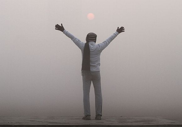 A man exercises as the sun rises amid dense fog on a cold winter morning