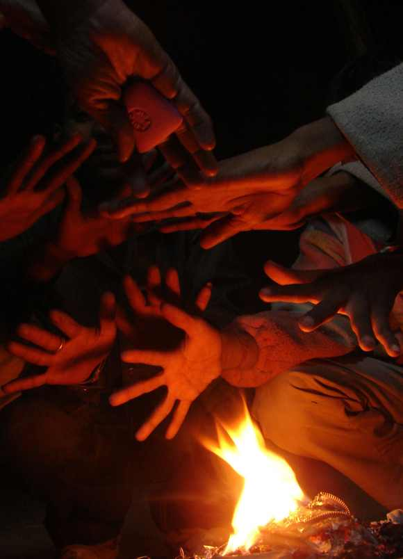 People warm their hands by a fire on a cold day in Allahabad, Uttar Pradesh