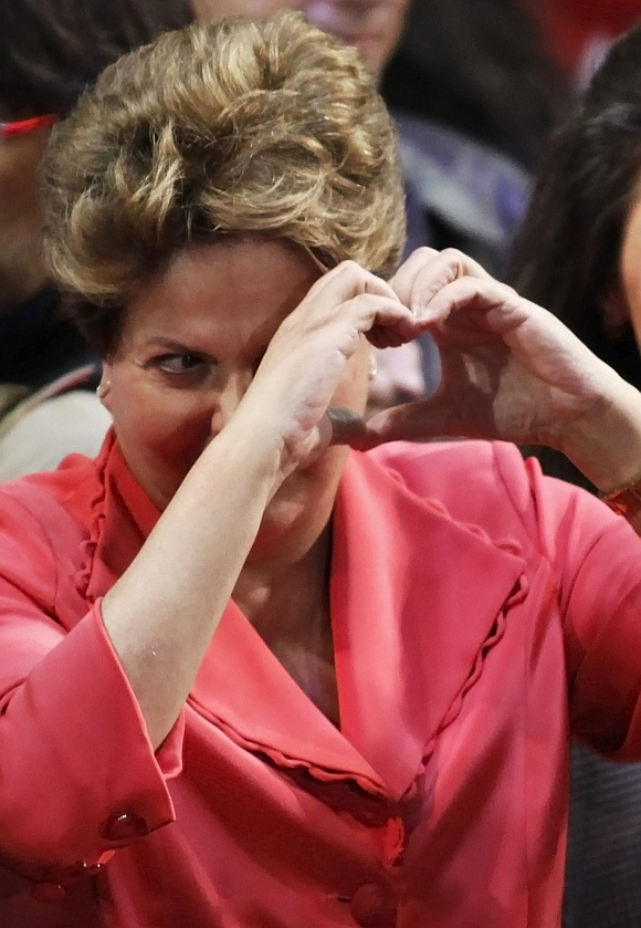 Brazil's President Dilma Rouseff of the Worker's Party shows a heart shape during a campaign rally in Sao Paulo