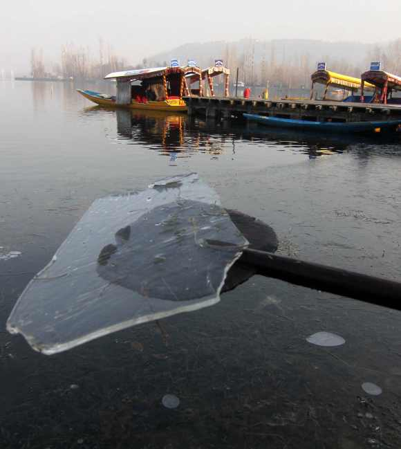 A boatman picks up ice formed on the Dal Lake with the help of his oar