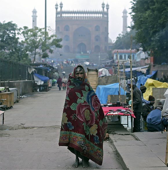A man wrapped up in a quilt walks in front of the Jama Masjid