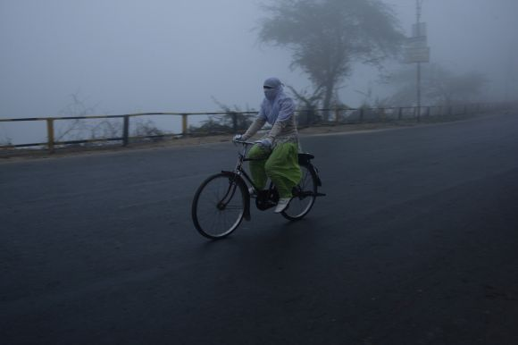 A girl cycles on a foggy and cold winter morning in Allahabad, Uttar Pradesh