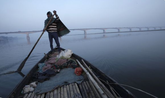 A man rows his boat in the waters of Ganga with Mahatma Gandhi Setu bridge seen in the background in Patna