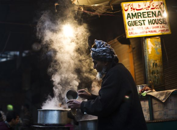 A vendor prepares tea at his roadside tea stall on a cold winter morning in the old quarters of Delhi