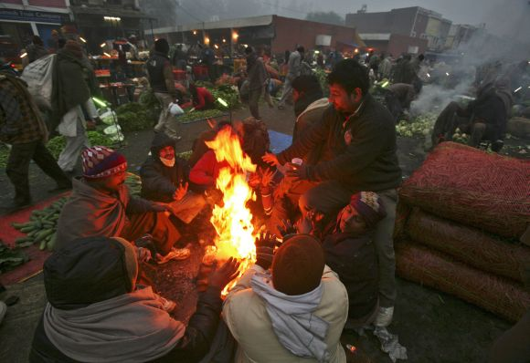 People warm themselves by a fire at a vegetable wholesale market on a cold winter morning in Chandigarh