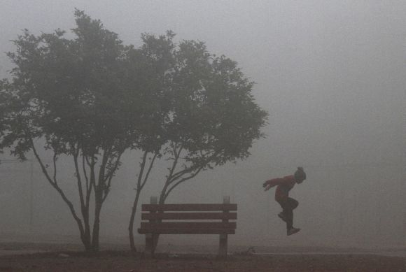 A boy plays at a park on a cold foggy morning in Chandigarh