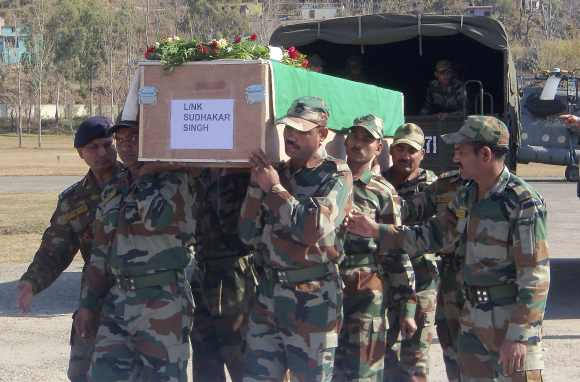 Indian Army soldiers carry a coffin containing the body of a colleague at a garrison in Rajouri district, about 170 km northwest of Jammu