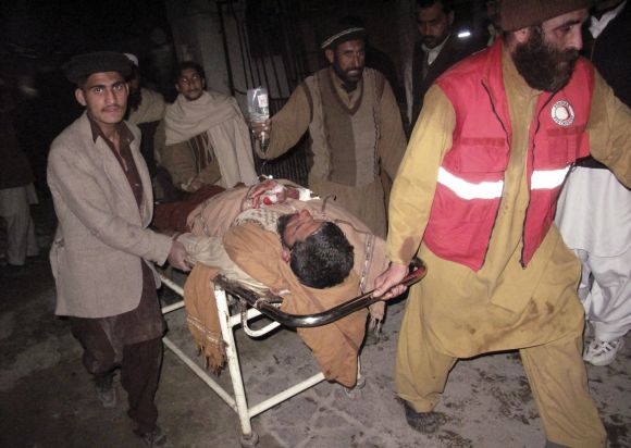 Rescue personnel wheel an injured man from the scene of a bomb explosion at Maki mosque in Takhtaband, on the outskirts of Mingora