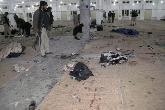 Police officials search for evidence at the scene of a bomb explosion at Maki mosque in Takhtaband, on the outskirts of Mingora, Swat Valley