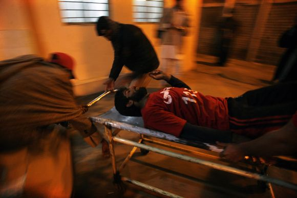 People wheel an injured rescue worker into a hospital after the second bomb blast in Quetta