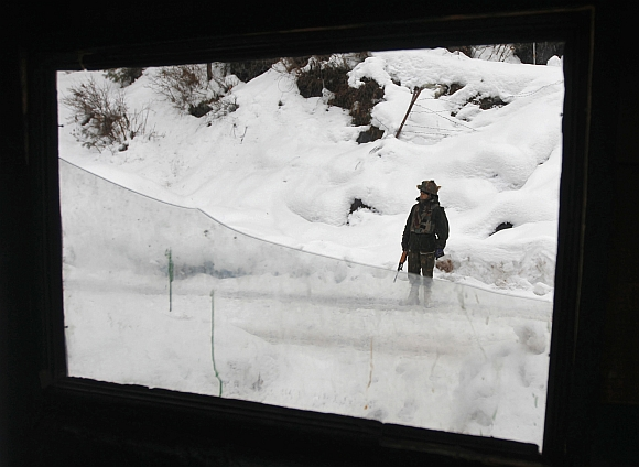 An Indian army soldier stands guard near the Line of Control in Churunda village, about 129 km northwest of Srinagar