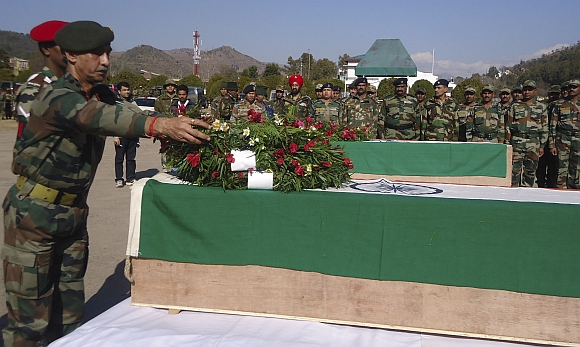 An Indian Army personnel places a wreath on a coffin containing the body of a colleague at a garrison in Rajouri district