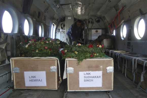 Two coffins containing the bodies of Indian Army soldiers are placed in a military helicopter at a garrison in Rajouri district
