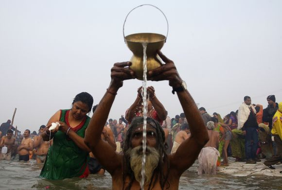 Devotees pray as they attend the first Shahi Snan at the ongoing Kumbh Mela in Allahabad on Monday