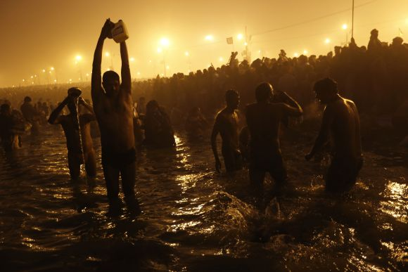Devotees pray as they attend the first 'Shahi Snan' at the ongoing Kumbh Mela in Allahabad