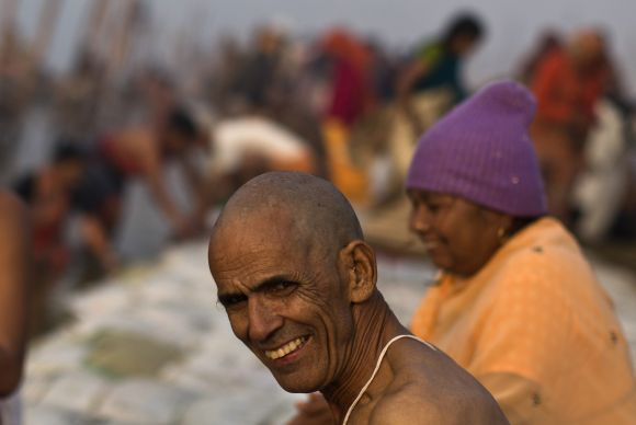 Devotees take part in the morning prayers on the banks of Ganga at the beginning of Kumbh Mela on Monday