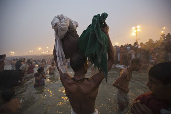 A devotee holds his belongings aloft as he attends the first Shahi Snan at the ongoing Kumbh Mela in Allahabad