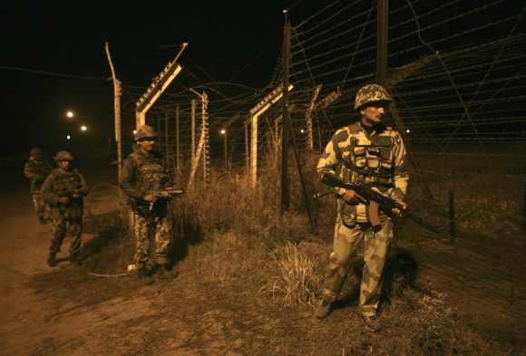 Border Security Force soldiers walk during night patrol near the fenced border with Pakistan in Abdullian, southwest of Jammu