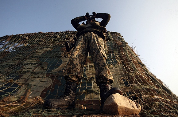 A Border Security Force soldier looks through a pair of binoculars outside a bunker near the fenced border with Pakistan in Suchetgarh, southwest of Jammu