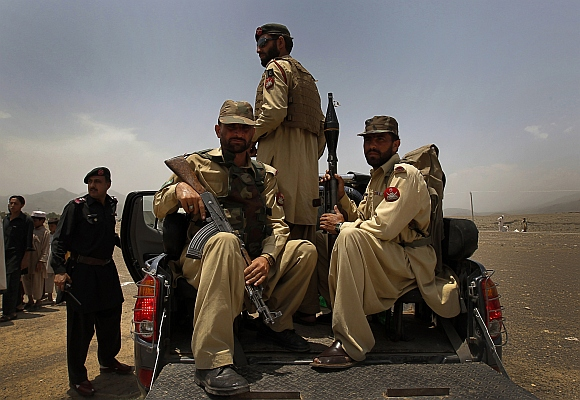 Pakistani soldiers stand guard along a road in Sadda a town in Kurram Agency located in Pakistan's Federally Administered Tribal Areas along the Afghanistan border