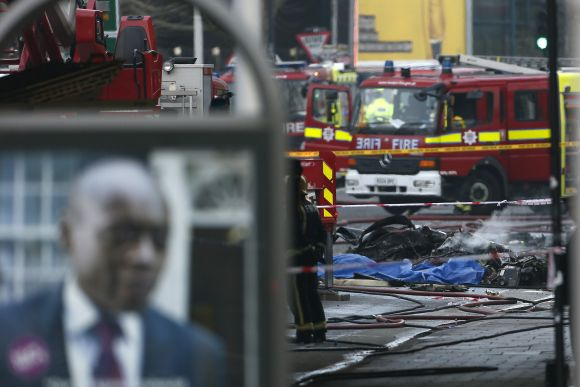 Smoke rises from debris as police and emergency services attend the scene of a helicopter crash in Vauxhall, south London