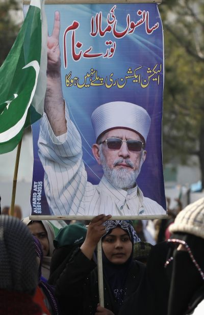 A supporter of Dr Tahir-ul Qadri holds poster during his speech in Islamabad on Wednesday