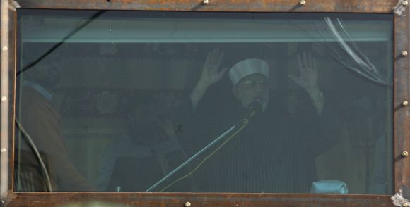 Dr Qadri addresses his supporters from behind the window of an armoured vehicle in Islamabad on Wednesday