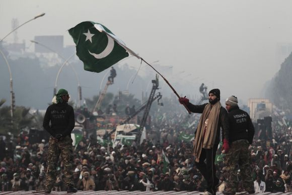 A supporter of Dr Qadri waves a Pakistani flag during protests in Islamabad