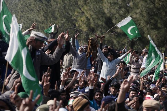 Supporters of Dr Tahir-ul Qadri wave flags during Qadri's speech in Islamabad on Wednesday