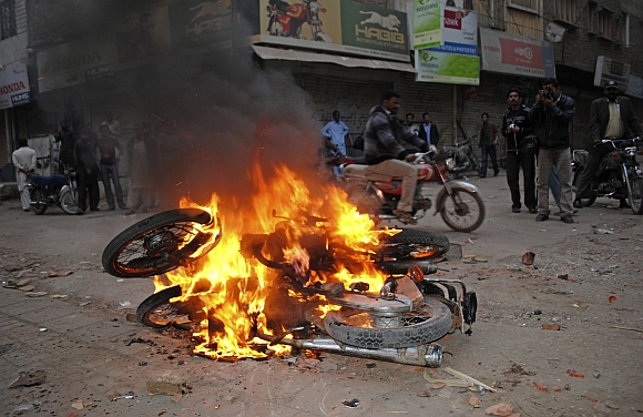A man rides past burning motorbikes, which were burnt by supporters of Pakistan People's Party to protest against a Supreme Court decision to arrest Prime Minister Raja Pervez Ashraf in Larkana