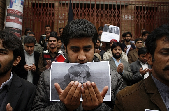 A journalist from the Balochistan Union Of Journalists holds a photograph of his colleague Imran Sheikh, who was killed in an explosion the day before, during a silent sit-in to protest against bomb blasts and condemn the killings of members of the media, outside the press club in Quetta