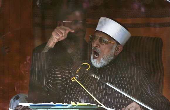 Dr Tahirul Qadri addresses his supporters from behind the window of an armoured vehicle during protests in Islamabad on Tuesday